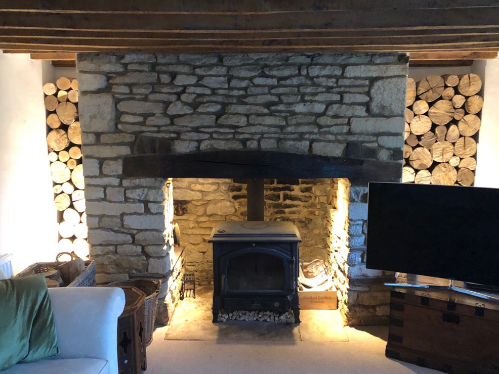 decorative hardwood logs in a fireplace alcove